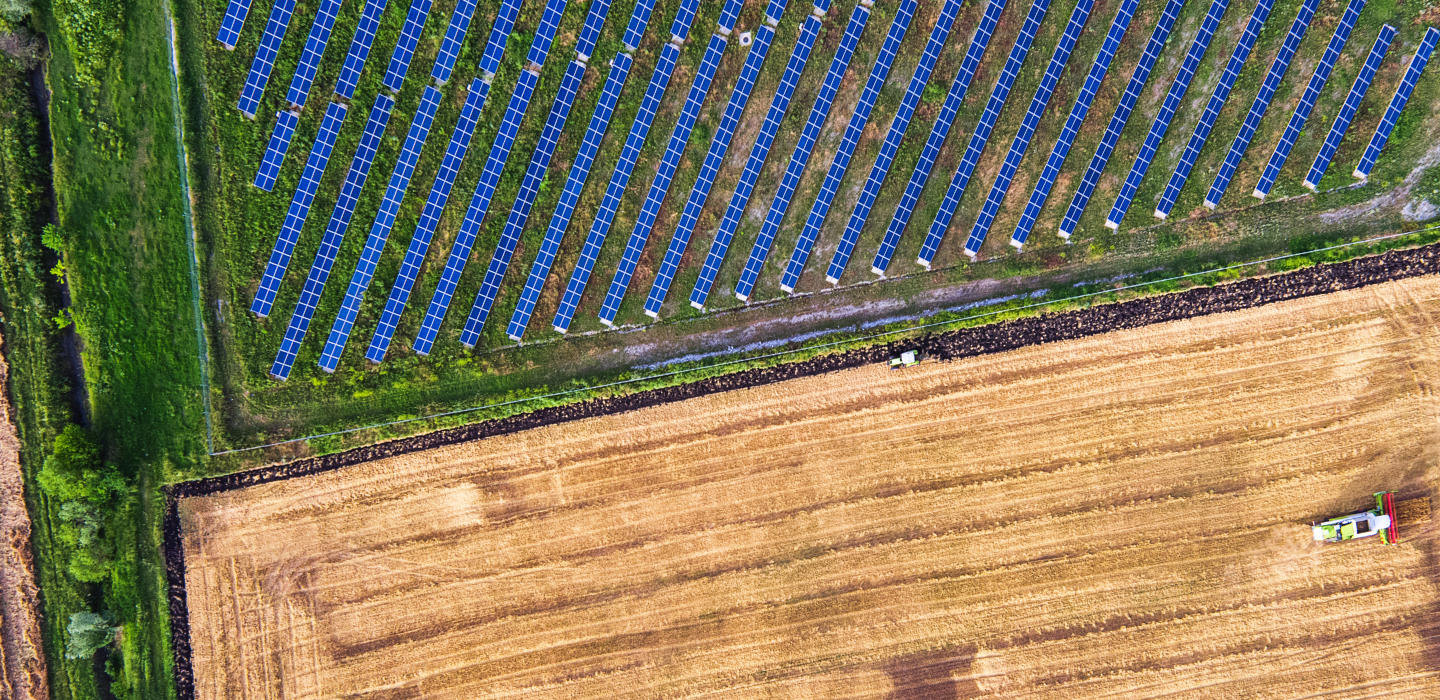 Overheard photo of a tractor ploughing a field, next to another field of solar panels
